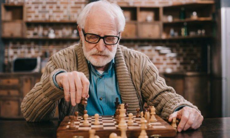 adulto mayor jugando ajedrez ejercicio mental para prevenir el alzheimer